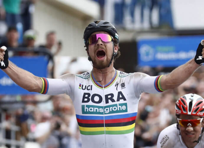 Peter Sagan tosses his arms up and yells in celebration as he wins a race wearing his rainbow striped Bora-Hansgrohe jersey