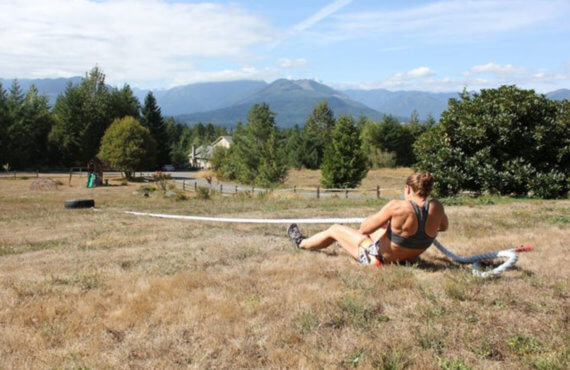 Becky Rogers pulling a tire with a rope from a seated position with a scenic mountain backdrop