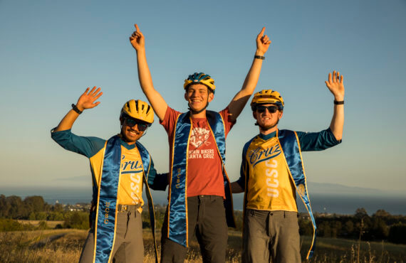 Three UCSC team members stand in celebration with their yellow helmets on along with their blue graduation sashes