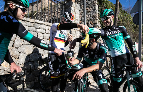 Members of Bora-Hansgrohe circle around a tub of Lemon Lime Osmo Active Hydration while one team member holds a banana peel