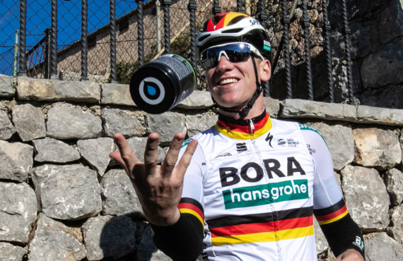 Bora-Hansgrohe cyclist poses tossing a tub of Osmo Lemon Lime Active Hydration in the air and catching it in his hand