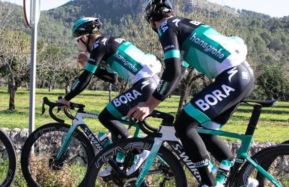 Two cyclists from the Bora-Hansgrohe cycling team ride their teal and black S-Works bikes long a scenic road