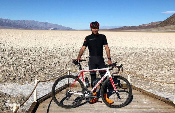 Chris Coble poses with his white and red Scott bike at the Badwater Basin in Death Valley National Park in California