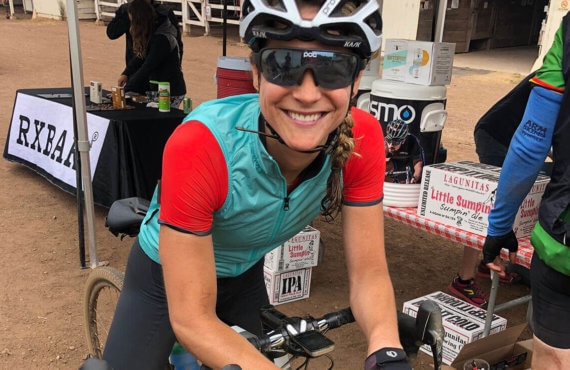 Lindsay Dwyer poses for a photo at the Osmo tent at a cycling event while wearing her red jersey with a green vest on