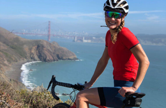 Lindsay Dwyer poses on her bike riding in the Marin Headlands with the Golden Gate Bridge and city of San Francisco in the background