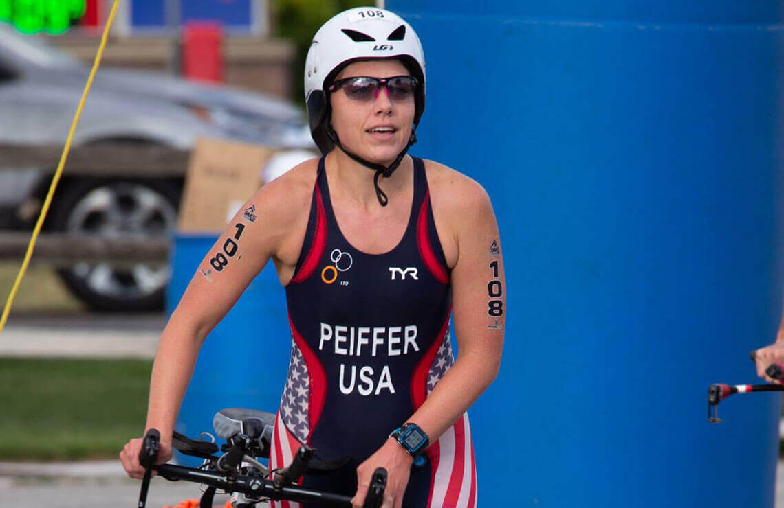 Roseann Peiffer walking with her bike after a race with the number 108 seen on her arms