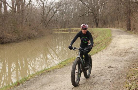 Roseann Peiffer riding a wide tire mountain bike on a dirt path around a pond