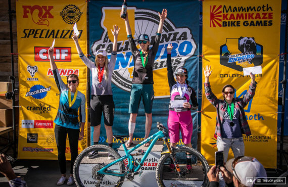Zephyr Sylvester stands on the podium along with four other women with a blue mountain bike in front