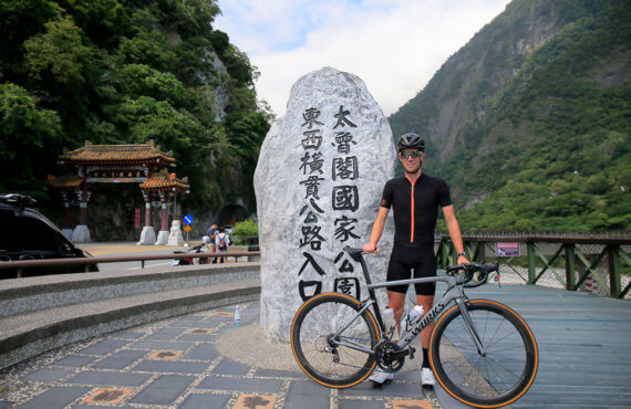 Camp Piper standing in Thailand wearing a black jersey and holding a gray Specialized S-Works bike with gum wall tires